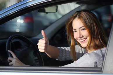 044114068-happy-woman-inside-car-gesturi
